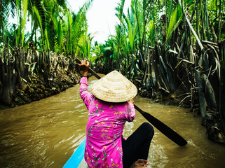 Traditional Vietnamese boat rowing down the Mekong Delta