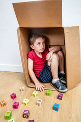 child sitting in box, thinking about school, seeking for confidence