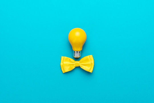 Top view photo of smart idea with yellow bulb and bow tie. Minimalist flat lay image of bow tie and lightbulb over turquoise blue background with copy space. Central composition of great idea concept.