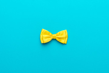 Minimalist flat lay photo of yellow satin bow tie over turquoise blue background and copy space. Top view and central composition of fashionable yellow men's accessory.