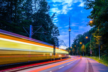 Germany, Illuminated tramway passing by street of traffic next to television tower of stuttgart city in green forest nature landscape in magical twilight mood after sunset