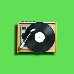 vintage turntable vinyl record player on green background. retro sound technology to play music