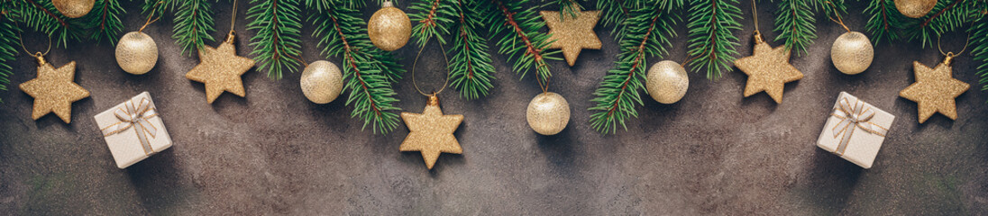 Christmas festive border, branch fir decorated with golden balls and stars, gift box, dark rustic background. Top view, flat lay.