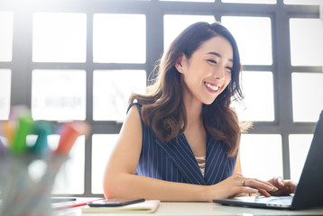 Portrait of smiling beautiful business asian woman with suit working in office desk using computer with copy space. Business people employee freelance online marketing e-commerce telemarketing concept