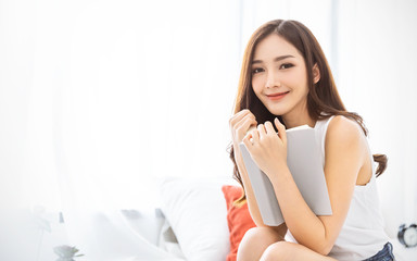 Portrait of young beautiful asian woman relax holding book in bedroom. Smile happy asian girl relaxing knowledge education university lifestyle, back to school concept Wall mural
