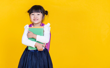 Portrait of young little asian girl hand holding books bag backpack isolated on yellow background with copy space. Education for toddler or preschool, childhood lifestyle back to school concept