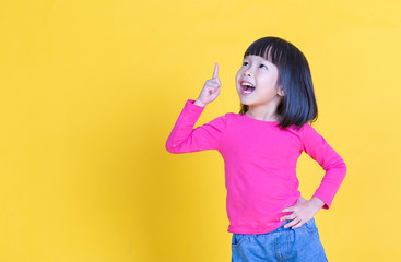 Portrait of young little asian girl hand point up isolated on yellow background with copy space. Education for toddler or preschool, childhood lifestyle back to school concept