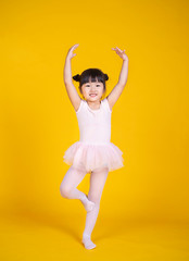 Portrait of little asian child girl dreams of becoming ballerina in a pink tutu skirt isolated on yellow background. Happy young girl practise her dance. Education childhood toddler lifestyle concept