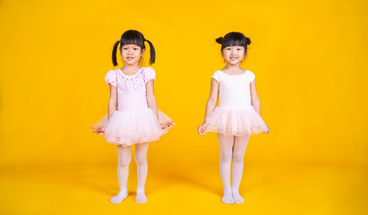 Portrait of little asian girls dreams of becoming ballerina in a pink tutu skirt isolated on yellow background. Happy young girl practise her dance. Education childhood toddler lifestyle concept