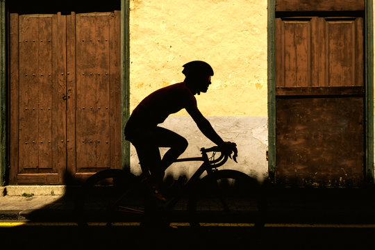 Silhouette of a male cyclist against old colonial house background