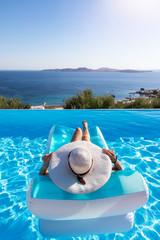 Sommerurlaubs Konzept: Unbekannte Frau mit weißem Hut entspannt in einem Pool auf einer Luftmatratze und genießt die Aussicht auf das Meer