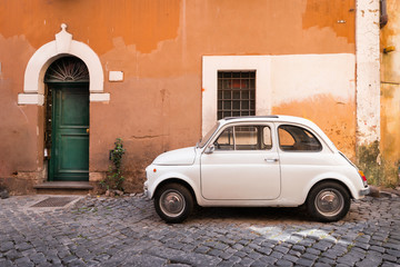 Photo sur Plexiglas Vintage voitures Vintage car parked in a cozy street in Trastevere, Rome, Italy, Europe.