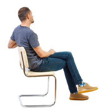 Side view of a man sitting on a chair.
