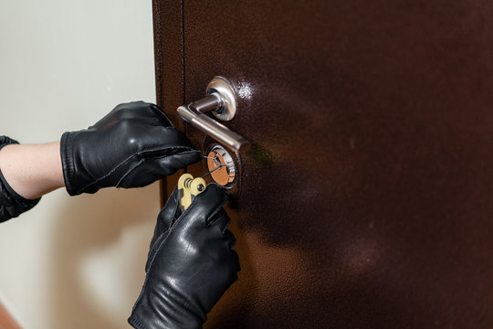 close up of a burglar with gloves picking a lock. Thief with a passkey.