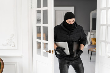 Thief with black balaclava stealing two modern expensive laptops. The burglar commits a crime in Luxury apartment with stucco. - fototapety na wymiar