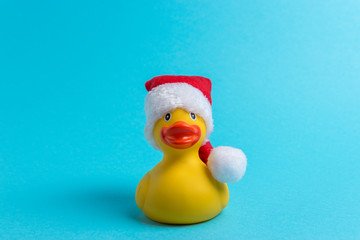 Rubber duck with Santa hat on blue background. Minimal Christmas or New Year concept.