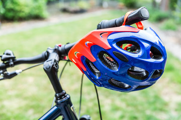 Bike helmet hangs from the handlebars of a bicycle