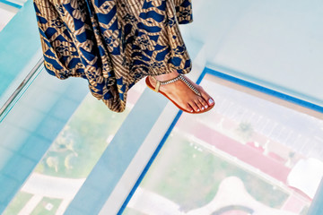 Woman stepping fith her feet on the glass floor at the Frame high above the ground