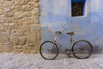 In de dag Fiets old bicycle in rustic town Street, Stone Wall and blue plaster