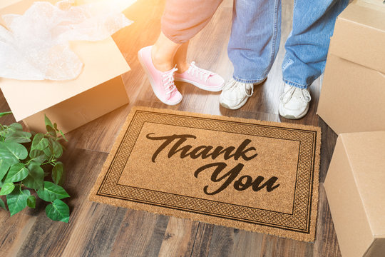 Man and Woman Unpacking Near Thank You Welcome Mat, Moving Boxes and Plant