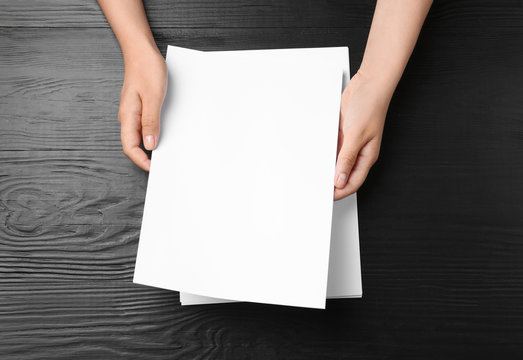 Woman holding blank paper sheets for brochure at black wooden table, top view. Mock up