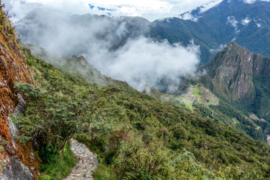 Stone steps on the steep slope of Machu Piccu Mountain with view on the Machu Picchu Inca citadel