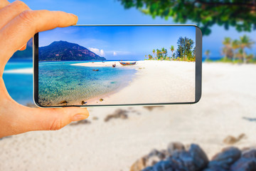 tropical beach picture on smartphone - travel concept - travel blog