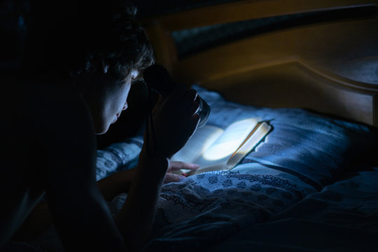 young person with a light torch reading books in bed at night in bedroom