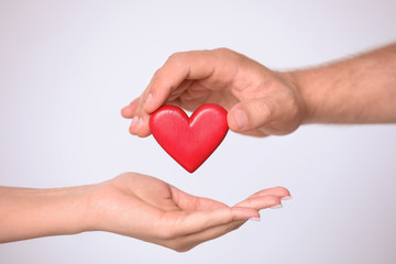 Man giving red heart to woman on white background, closeup. Donation concept
