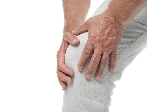 Senior man having knee problems on white background, closeup