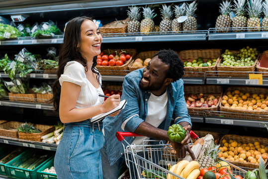 happy african american man looking at asian woman with notebook near shopping cart with groceries