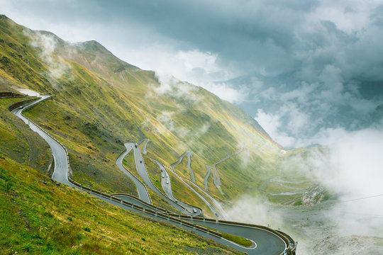 Passo dello Stelvio. Serpentine mountain road in Italy. Foggy weather, very cloudy. Rainbow.
