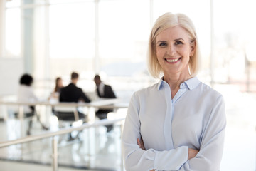 Head shot portrait smiling mature businesswoman posing in office hallway