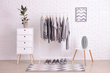 Rack with hanging clothes in interior of dressing room Wall mural