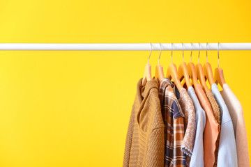 Rack with hanging clothes on color background Wall mural