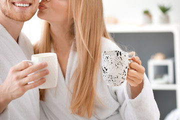 Wall Mural - Morning of happy young couple in bathrobes drinking coffee at home