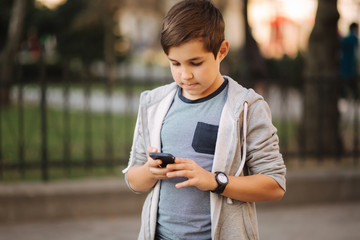 Young boy playing with smaptphone. Schoolboy using mobile phone on the street