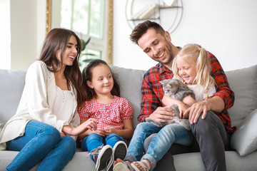 Happy family with cute cat resting at home