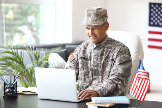 Mature male soldier working with laptop in headquarters building
