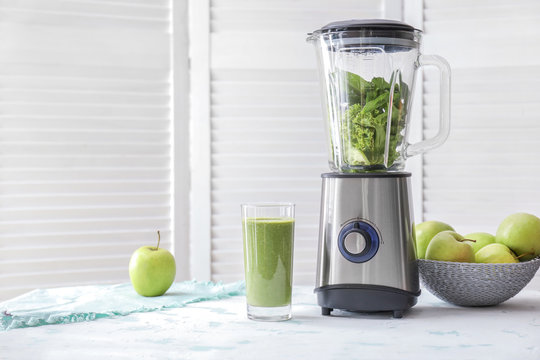 Glass of healthy smoothie and blender with ingredients on table