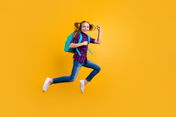 Full length side photo of little pupil jump high glad return school wear casual checkered shirt jeans denim isolated yellow background