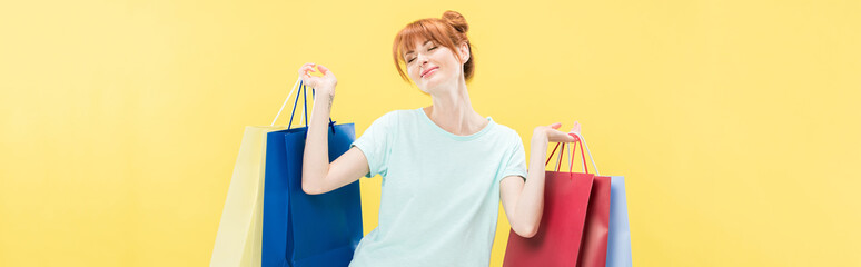panoramic shot of smiling redhead girl holding shopping bag isolated on yellow