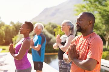 Mature people meditating together at park