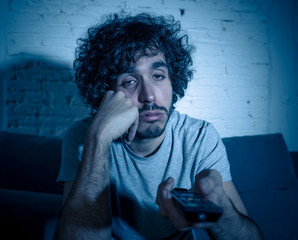 Lifestyle portrait of young millennial man watching boring tv feeling sleepy at night