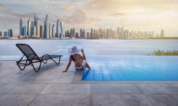 Beautiful panorama of Dubai Marina skyline in a background with a pool, deck chair and woman with a white hat at sunset.