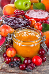 Jams of cherries, apricots and blueberries with decoration of fruits