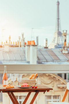 Paris luxury lifestyle. Pink wine, two glasses, traditional french bakery products and strawberries on a balcony. Toned image in vintage colors