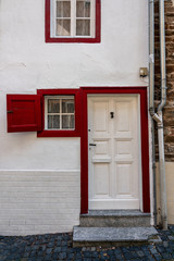 white entrance door with red frame