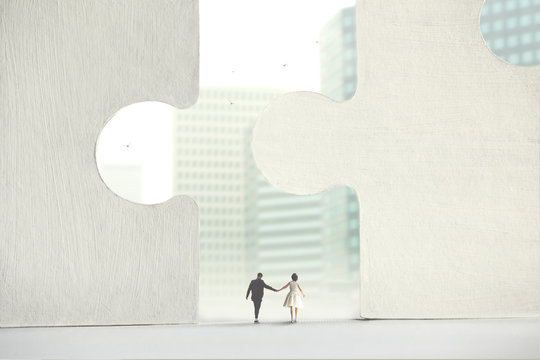 couple who pass under a perfect interlocking of giant puzzles, concept of perfect love