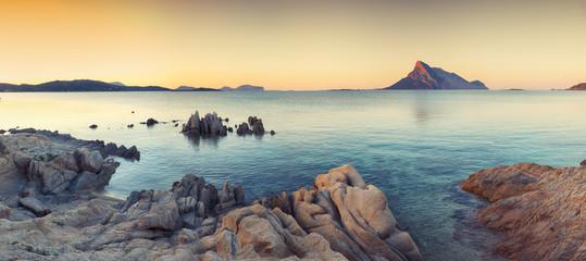 Fantastic azure water with rocks near beach Porto Taverna at sunset